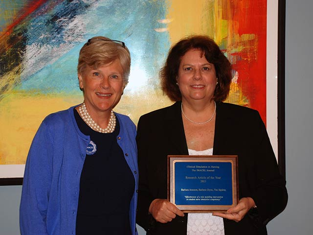 Dr. Barbara Aronson poses with her award for 2013 Research Article of the Year