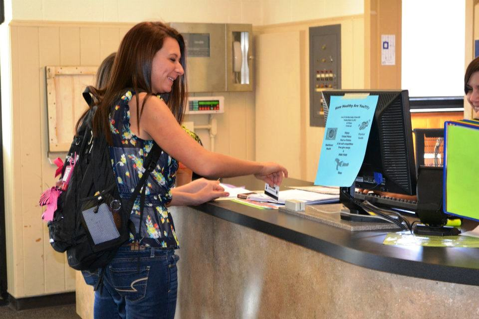 Girl swiping card at residence hall front desk