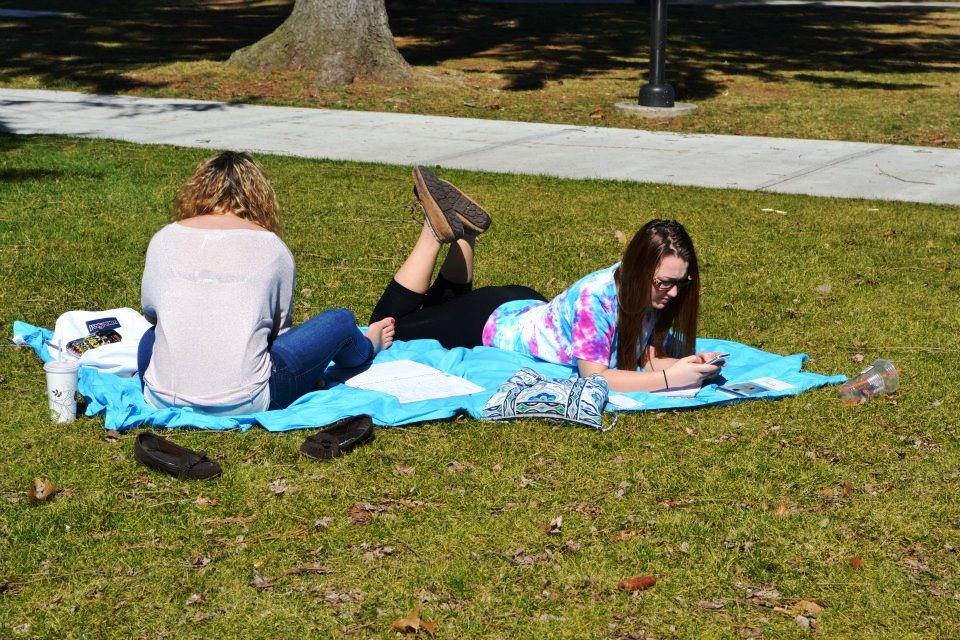 Two girls laying outside on a blanket studying