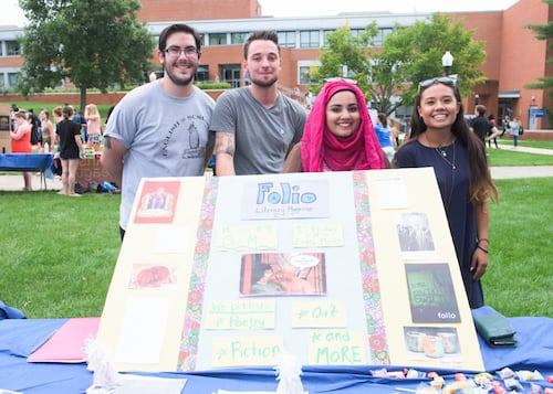 Four students with a sign representing Folio Literary Magazine club