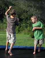 Two boys jumping on a trampoline
